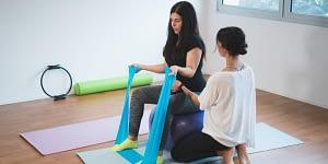 Pilates Teacher Assisting Client